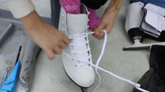 A girl ties the laces on white skate, visible only hands and leg - stock footage