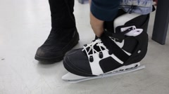 Boy tries on black skates in the store, visible only hands and leg Stock Footage