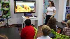 The teacher leads lesson next to the display in center for children Stock Footage