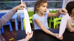 Girl listens attentively and folds a sheet of paper Stock Footage
