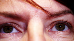 Closeup of woman's face and eyes, removing a lock of hair from his forehead Stock Footage