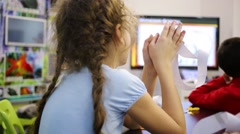 Girl with a strip of paper in hands sits and listening to teacher Stock Footage