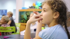 Girl listens attentively to the teacher in the classroom Stock Footage