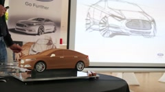 A clay model of the car next to the display showing pencil drawings Stock Footage