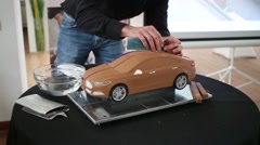 Man shows how to make a clay model of the car Stock Footage