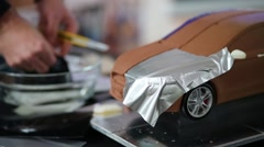 A miniature model of the car, on the background a man wets paper Stock Footage