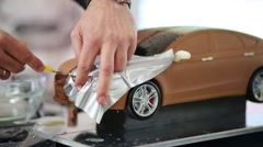 Man cuts foil and spreads it on the hood of the car model Stock Footage