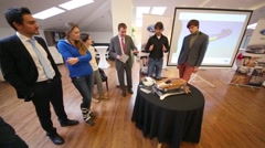 People stand around a table with a miniature model of a car Stock Footage