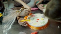 The children hands are painting on the cake Stock Footage