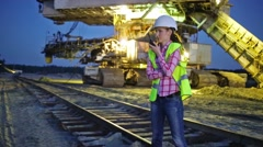 Female worker is talking on walky-talky near career stacker. Stock Footage