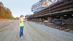 A female worker talks on walky-talky next to the train. Stock Footage