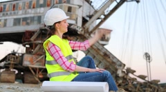 A female worker is sitting near the career Stacker. Stock Footage