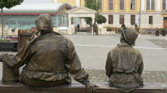 Bronze statues of a woman and a boy sitting on a bench in Alba Iulia fortress - stock footage