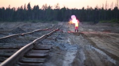 The female worker is running with a red signal light near railway Stock Footage