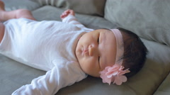 A wiggling newborn baby laying on a couch - stock footage