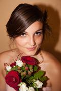 Portrait of an happy and pretty woman with bouquet of red and white flowers - stock photo