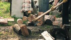 Lumberjack cuts wood logs with splitting axe Stock Footage