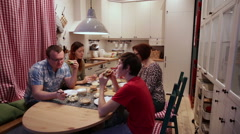 The family at table eating hamburgers and talking - stock footage