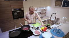 Man cuts the sausages on the Board and lay in pan Stock Footage