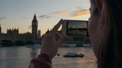A young woman excitedly takes photos of London attractions on her phone. Stock Footage