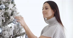 Stylish woman admiring a Christmas tree Stock Footage