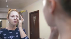 Stock Video Footage of Beautiful red-haired girl puts on face make-up before a mirror