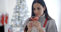 Pretty young woman enjoying her Christmas baking Stock Footage