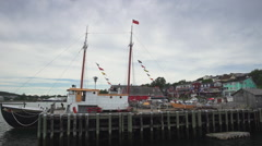 A tourist sailboat docked on the waterfront of Nova Scotia's historic Lunenburg Stock Footage
