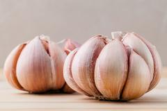 Close Up organic garlic with selective focus on the teak wood background - stock photo