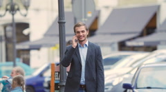 The businessman walks around the city and communicates by the phone. - stock footage