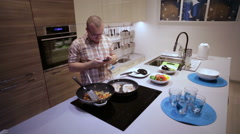 Man cooking and looking at the phone Stock Footage