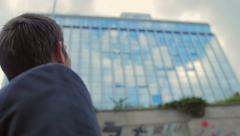 The businessman watches on big glass buildings Stock Footage