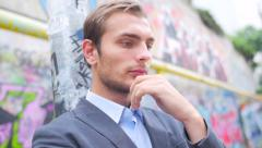 The young man in a suit costs one on the street and looks very serious - stock footage