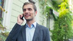 The businessman costs in the downtown and communicates with someone by phone - stock footage