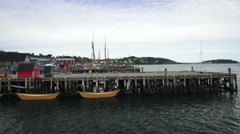 Yellow dories floating by a wooden pier in downtown Lunenburg Stock Footage