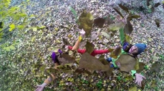 Top view of three kids throw leaves up. Top view SLOW MOTION Stock Footage