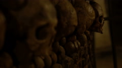 Rack focus shot of human skulls in an underground ossuary. Stock Footage