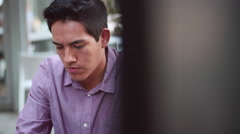 A young man sitting outside and looking down at his phone - stock footage