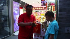 Chinese master making the candy from molten sugar, Xianyukou street, Beijing Stock Footage