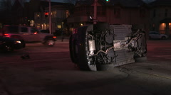 Car accident with car rolled over on it's side at city intersection at dusk Stock Footage