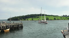 A Schooner crew hoists it's sails in Lunenburg Harbour Nova Scotia - stock footage