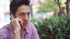 A young man sitting outside talking on his phone and drinking coffee - stock footage