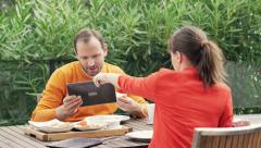 Young couple using modern tablet during breakfast on terrace Stock Footage