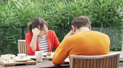 Offended, bored couple sitting by table during breakfast on terrace Stock Footage