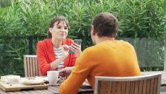 Young, happy couple using smartphone during breakfast on terrace Stock Footage