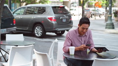 A young man sitting outside using a tablet and drinking coffee Stock Footage