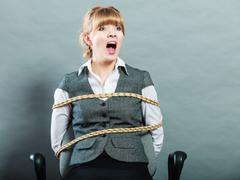 Afraid kidnapped woman tied with rope to chair. - stock photo