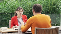 Young couple talking and eating breakfast on terrace Stock Footage