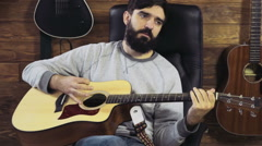handsome bearded man playing the acoustic guitar slow motion - stock footage