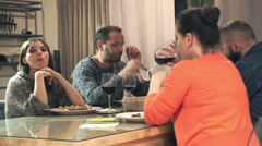 Bored, sad friends drinking red wine by table at home Stock Footage